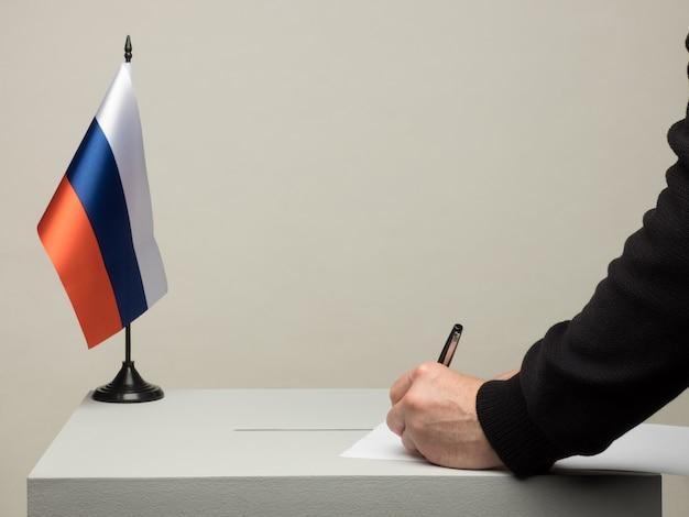 Urna com a bandeira nacional da rússia. eleição presidencial em 2018. mão lançando uma cédula