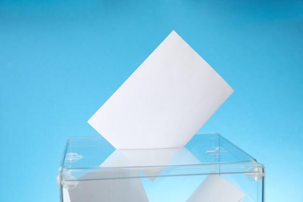 Urna de votação com boletins na superfície azul