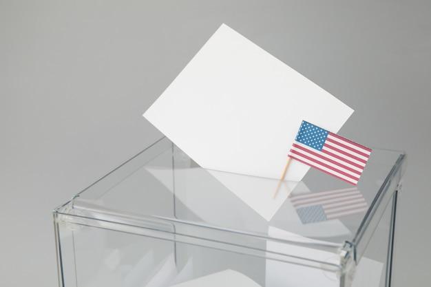 Urna de voto com boletins e bandeira americana na superfície cinza
