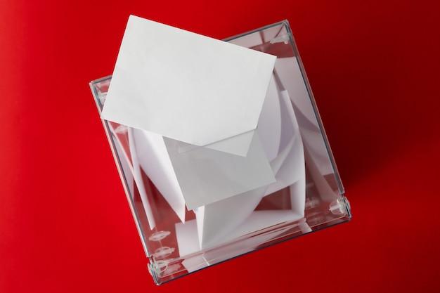 Urna de voto com boletins sobre fundo vermelho, vista superior
