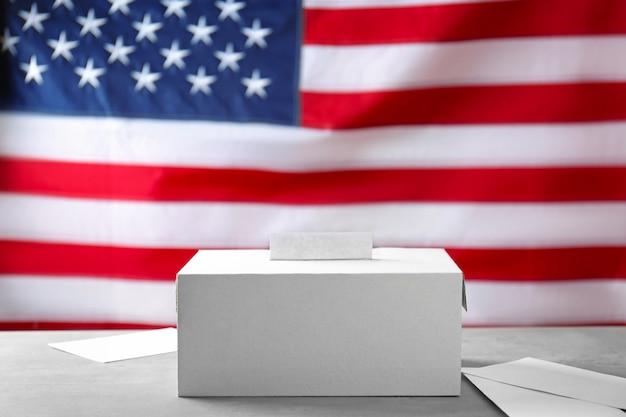 Urna eleitoral e envelopes no fundo da bandeira nacional dos eua