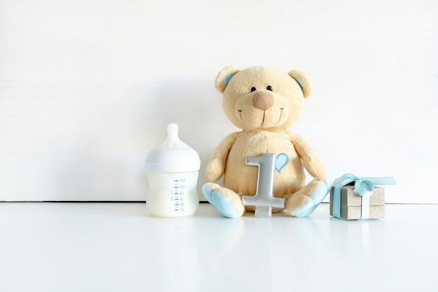 Ursinho de pelúcia brinquedo, caixa de presente, dígito um na mesa branca com espaço de cópia. chá de bebê, acessórios, decorações, coisas, presentes para menino, menina, primeiro ano, feliz aniversário, primeiro plano de fundo da festa do recém-nascido