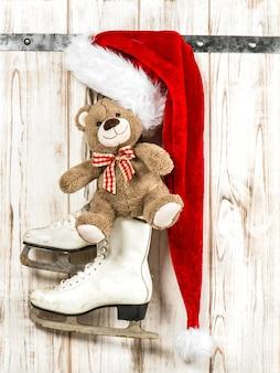 Ursinho de pelúcia, chapéu de papai noel vermelho e patins de gelo brancos. decoração de natal estilo vintage