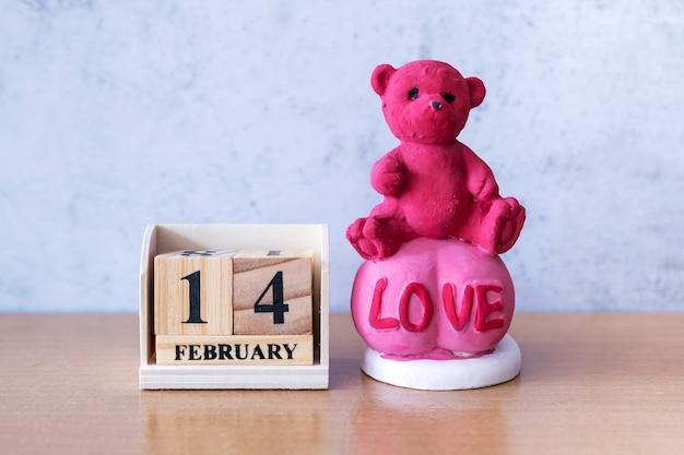 Ursinho de pelúcia com calendário de madeira, 14 de fevereiro. dia dos namorados