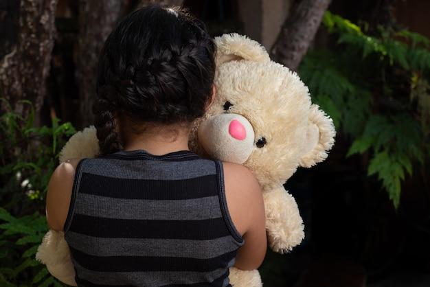 Ursinho de pelúcia, criança brasileira brincando com muito carinho com seu ursinho de pelúcia, foco seletivo.