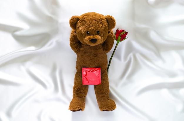 Ursinho de pelúcia deitado na cama com pacote de preservativo para o conceito de saúde sexual mundial de sexo seguro e dia de aids