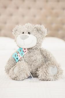 Ursinho de pelúcia e bebê na cama