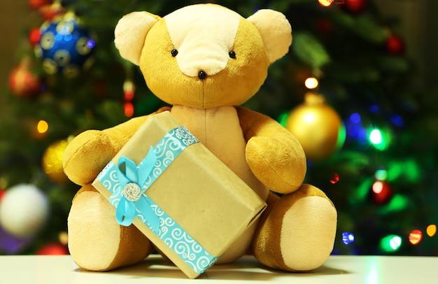 Ursinho de pelúcia e caixa de presente no fundo da árvore de natal
