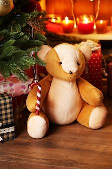 Ursinho de pelúcia e caixas de presente perto da árvore de natal, close-up