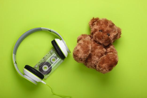 Ursinho de pelúcia e fones de ouvido estéreo com fita cassete em uma superfície verde