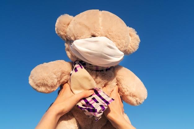 Ursinho de pelúcia em uma máscara protetora nas mãos femininas contra o fundo do céu, o conceito de um vírus, proteção contra infecções, cautela, segurança