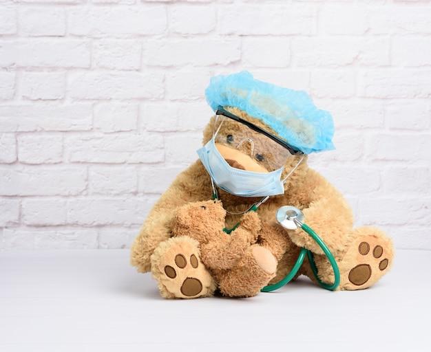 Ursinho de pelúcia marrom sentado em óculos de proteção de plástico, uma máscara médica descartável e um boné azul, conceito de pediatria