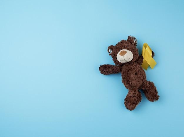 Ursinho marrom tem na pata uma fita amarela dobrada em um loop