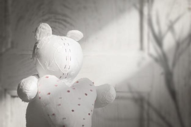 Urso artesanal com coração nas mãos, vintage branco macio para papel de parede dia dos namorados.