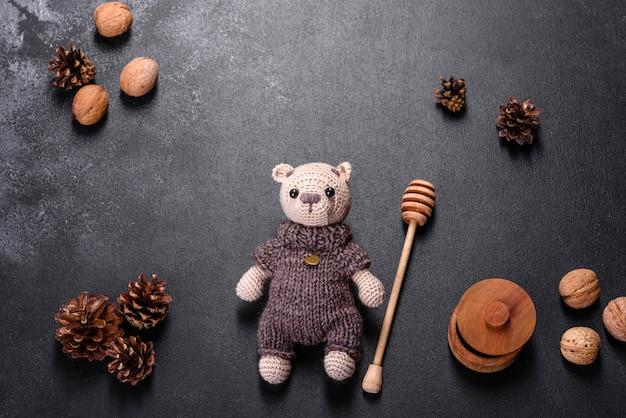 Urso de brinquedo amarrado com fios de lã em uma mesa escura. trabalho manual, hobby