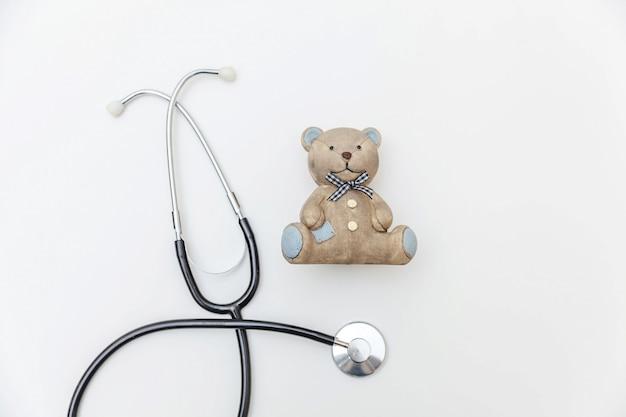 Urso de brinquedo de design simplesmente simples e estetoscópio de equipamento de medicina isolado