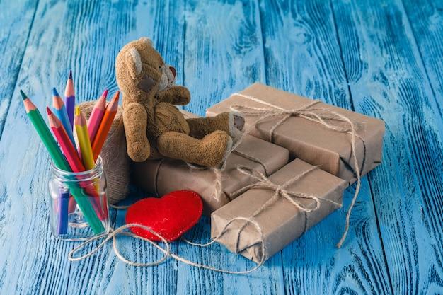 Urso de brinquedo e alguns pacotes de papel embrulhados na mesa de madeira