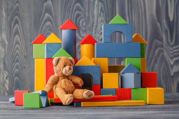 Urso de brinquedo e empilhar blocos de madeira