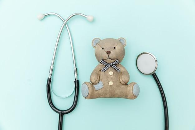 Urso de brinquedo e estetoscópio de equipamento de medicamento isolado