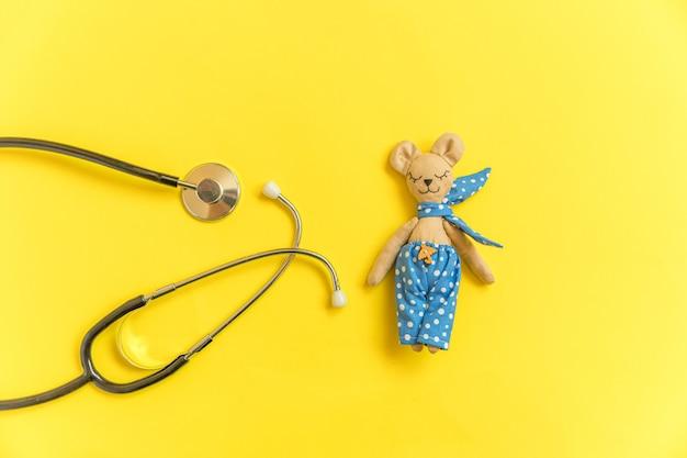 Urso de brinquedo e estetoscópio de equipamento de medicina isolado na mesa amarela