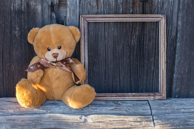 Urso de brinquedo senta-se em uma mesa e ao lado de um quadro vazio de madeira