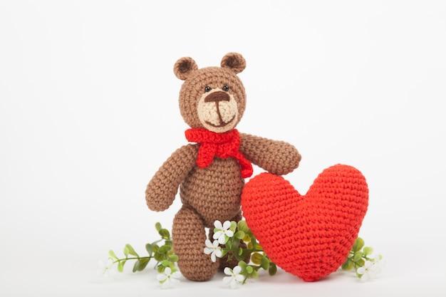 Urso de malha com um coração. decoração de são valentim. brinquedo de malha, amigurumi, cartão de felicitações.