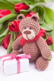 Urso de malha. decoração festiva. tulipas vermelhas delicadas. dia dos namorados. artesanal, brinquedo de malha, amigurumi