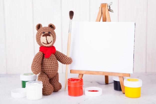 Urso de malha marrom com pincel e tinta perto do cavalete. trabalho manual, criatividade. amigurumi. cartão postal