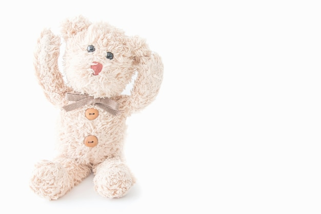 Urso de peluche bonito deitado no fundo de tecido branco.