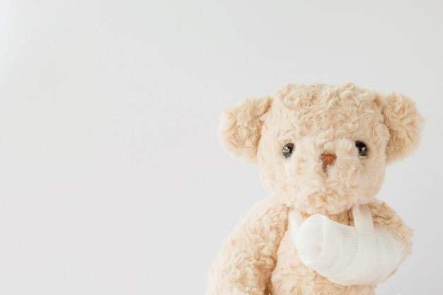 Urso de peluche com braço enfaixado