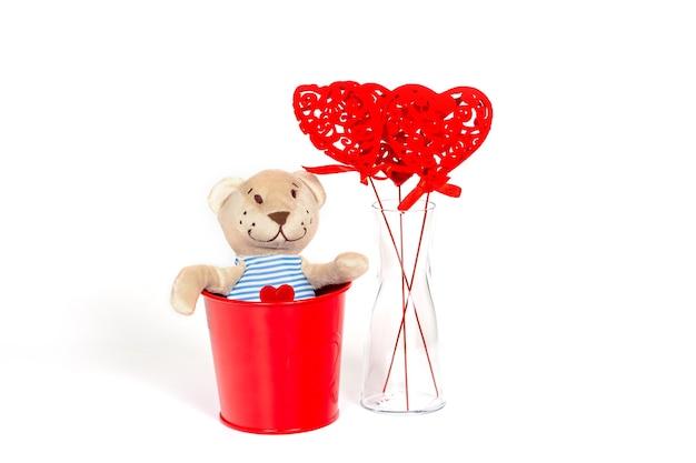 Urso de peluche com coração bordado num balde de metal vermelho. conceito de dia dos namorados