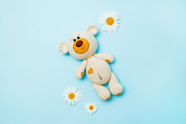 Urso de peluche feito a mão de amigurumi com as margaridas isoladas em um fundo azul. fundo de bebê copie o espaço, vista de cima.