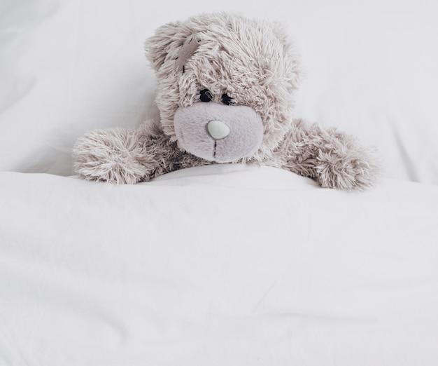 Urso de pelúcia alto ângulo na cama