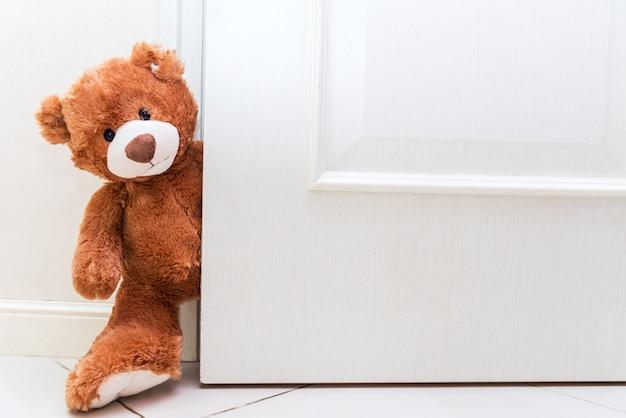 Urso de pelúcia atrás da porta aberta. as crianças brincam com brinquedos de pelúcia. copie o espaço na porta branca.