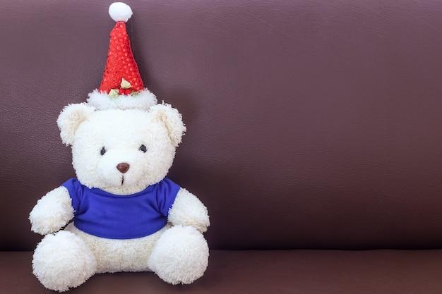 Urso de pelúcia branco com camisa azul usando chapéu de natal no sofá