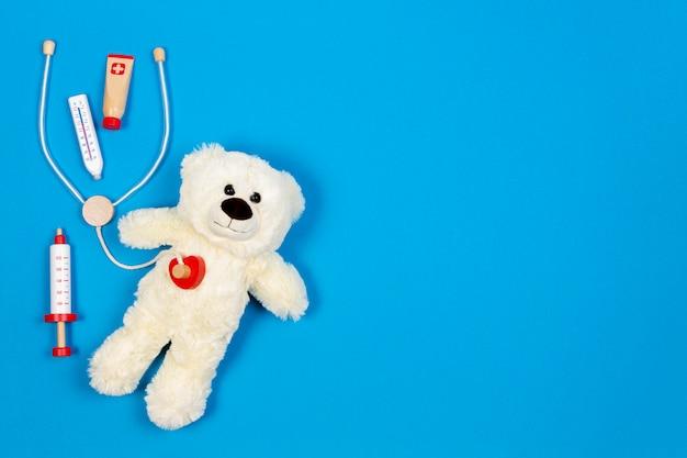 Urso de pelúcia branco com estetoscópio de brinquedo e ferramentas de medicina de brinquedo