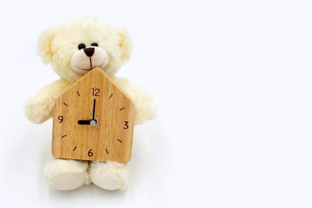 Urso de pelúcia branco com relógio de madeira na superfície branca