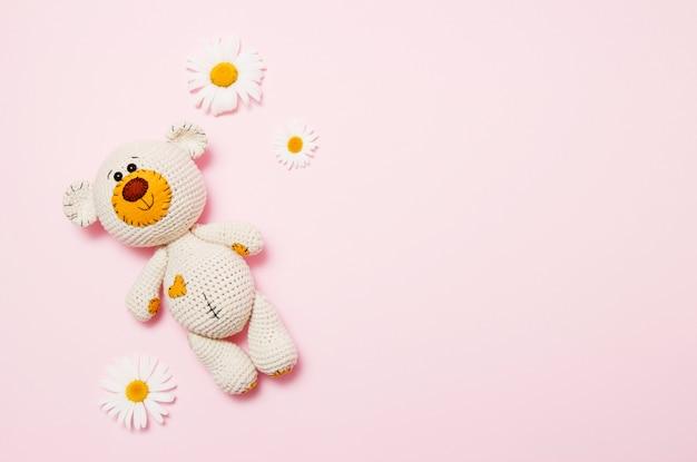 Urso de pelúcia brinquedo com margaridas isolado em rosa