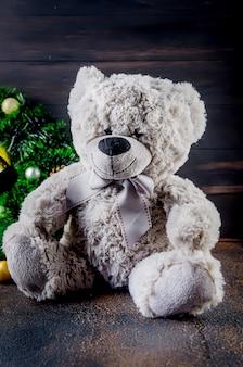 Urso de pelúcia cinza com caixa de presente e coroa de flores