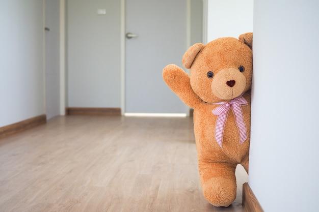 Urso de pelúcia com cabelos castanhos atrás da porta aberta. plano de fundo para as crianças brincam ursinho de pelúcia