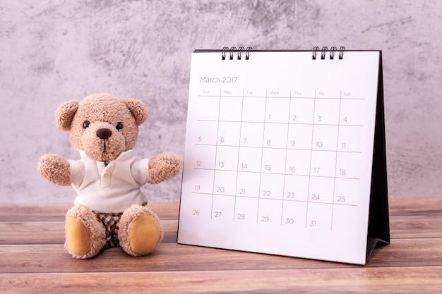 Urso de pelúcia com calendário na mesa de madeira.