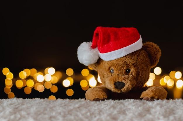 Urso de pelúcia com chapéu de papai noel com luzes de natal.