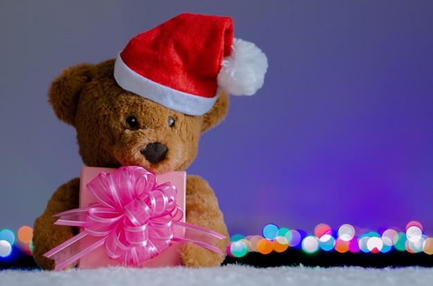 Urso de pelúcia com chapéu de papai noel, segurando o foco parcial da caixa de presente de natal.