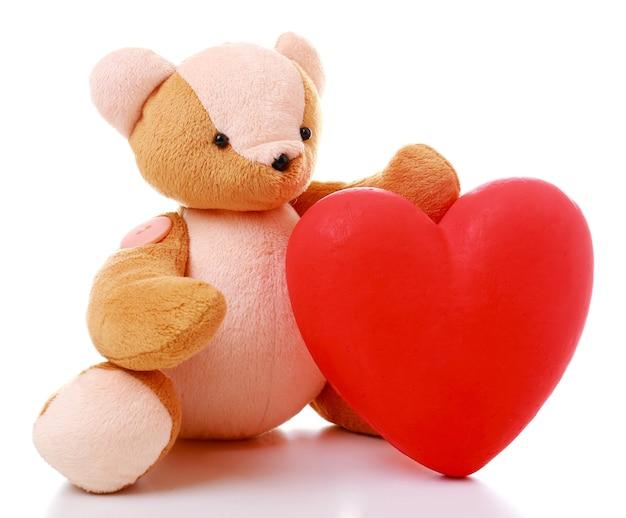 Urso de pelúcia com coração vermelho em branco