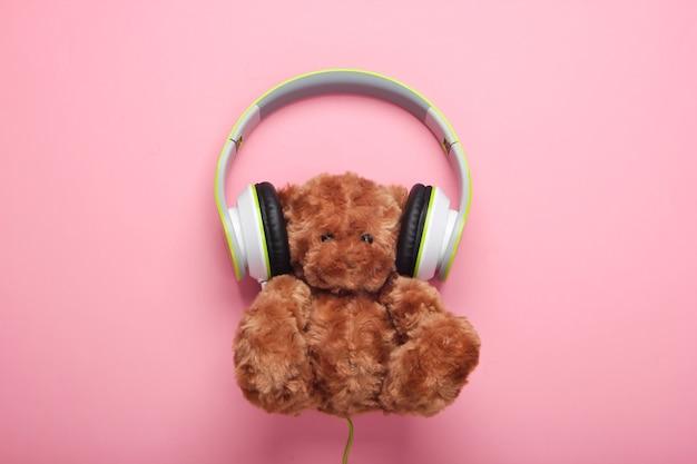 Urso de pelúcia com fones de ouvido estéreo em superfície rosa pastel