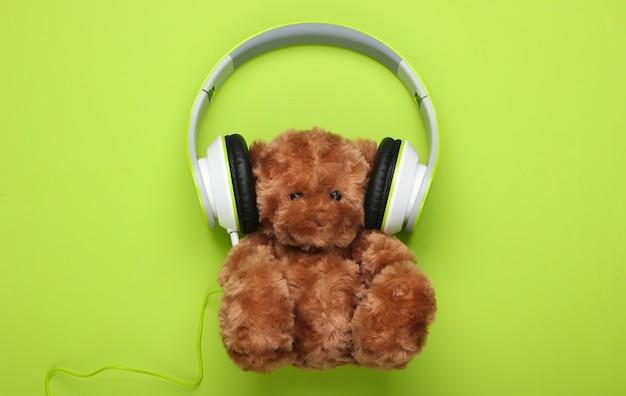 Urso de pelúcia com fones de ouvido estéreo em uma superfície verde