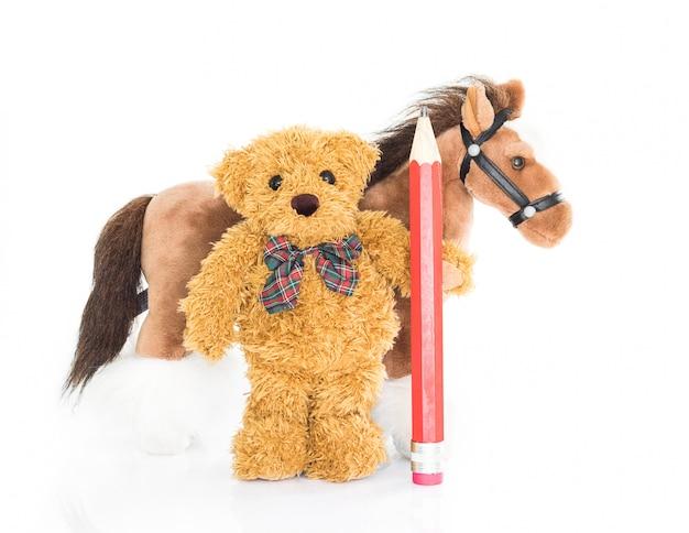 Urso de pelúcia com lápis vermelho e cavalos