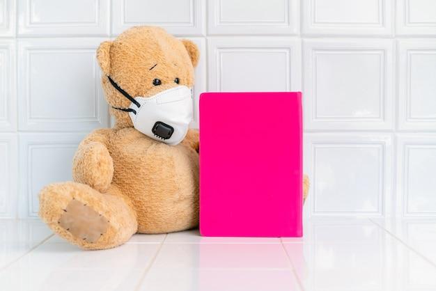 Urso de pelúcia com máscara facial e caderno rosa sobre fundo branco.