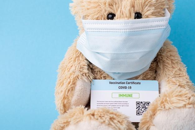 Urso de pelúcia com máscara protetora segurando certificado de vacinação
