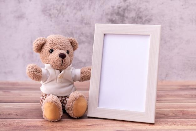 Urso de pelúcia com moldura na mesa de madeira. celebração do dia dos namorados